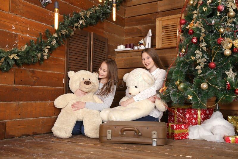 Deux filles s'asseyent sur le plancher sur le fond d'un mur en bois près de l'arbre de Noël image libre de droits