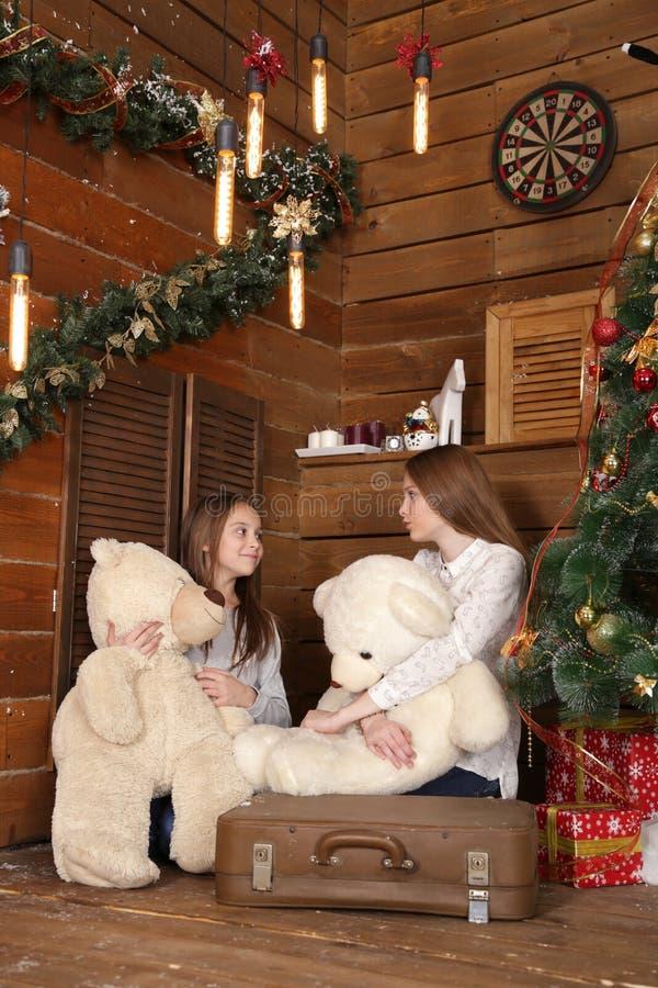 Deux filles s'asseyent sur le plancher sur le fond d'un mur en bois près de l'arbre de Noël images libres de droits