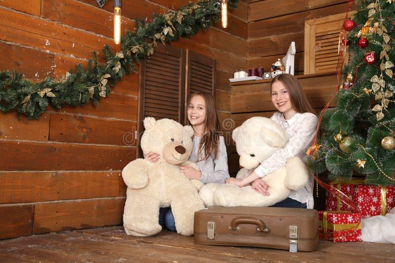 Deux filles s'asseyent sur le plancher sur le fond d'un mur en bois près de l'arbre de Noël image stock