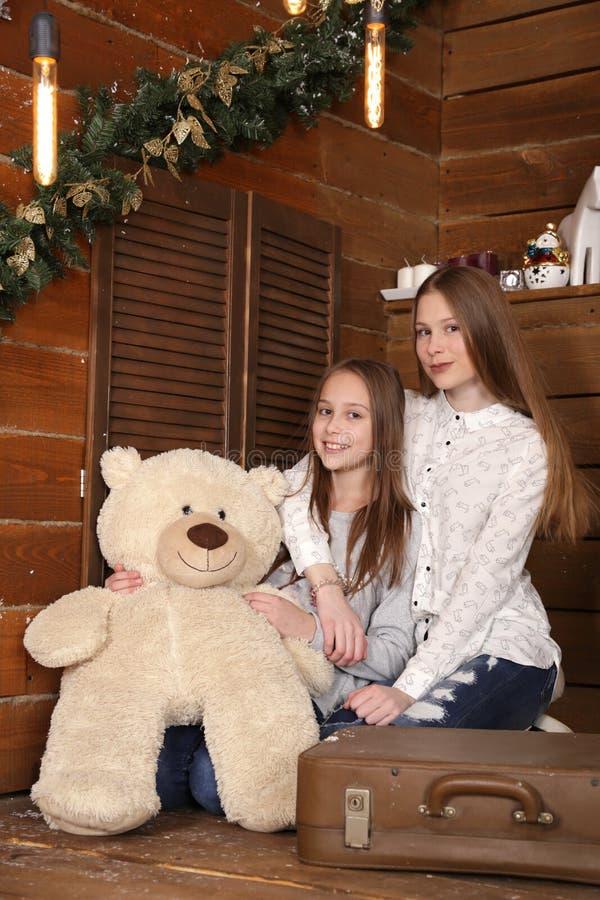 Deux filles s'asseyent sur le plancher sur le fond d'un mur en bois près de l'arbre de Noël photo stock