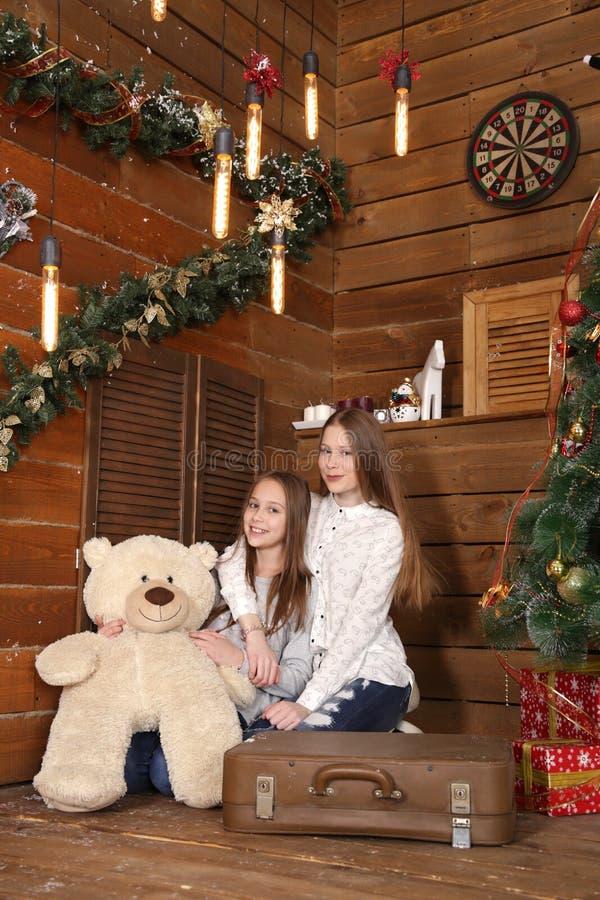 Deux filles s'asseyent sur le plancher sur le fond d'un mur en bois près de l'arbre de Noël photo libre de droits