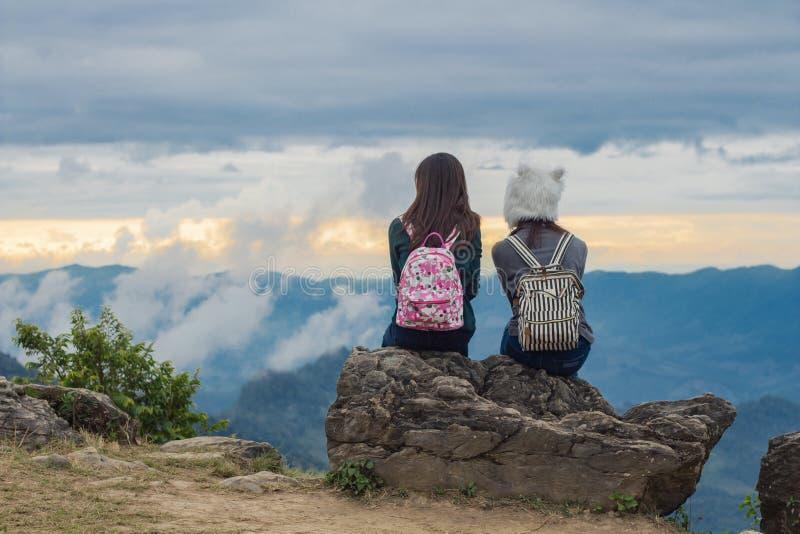 Deux filles s'asseyent sur une roche se regardant, le ciel bleu avec des nuages et vue d'arbres verts la belle de ci-dessus le ph image stock