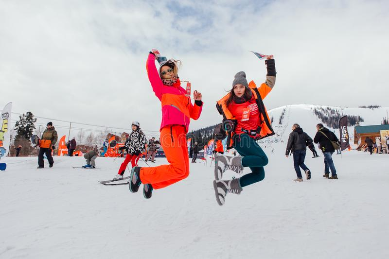 Deux filles sautant sur la pente de neige image stock