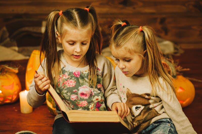 Deux filles se préparant aux vacances Nuit, bougies, potiron, contes images libres de droits