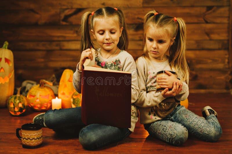 Deux filles se préparant aux vacances Nuit, bougies, potiron, contes images stock