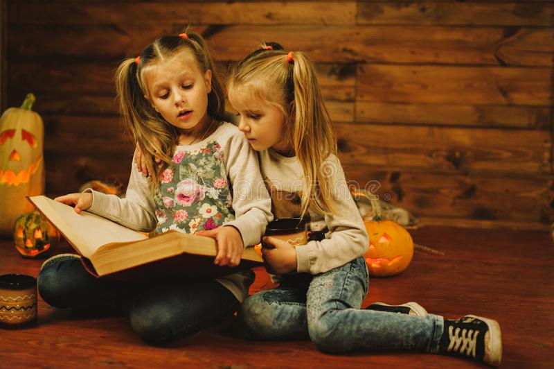 Deux filles se préparant aux vacances Nuit, bougies, potiron, contes photographie stock libre de droits