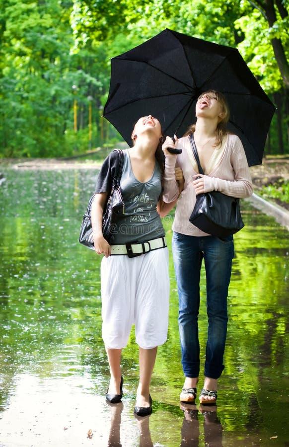 Deux Filles Se Réjouissent Au Temps Pluvieux Photos stock