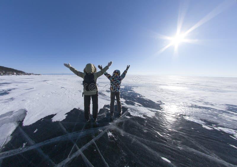 Deux filles se tenant sur la glace du lac congelé avec ses mains  Baikal Sibérie Russie Les gens embrassant la nature avec ouvert images libres de droits