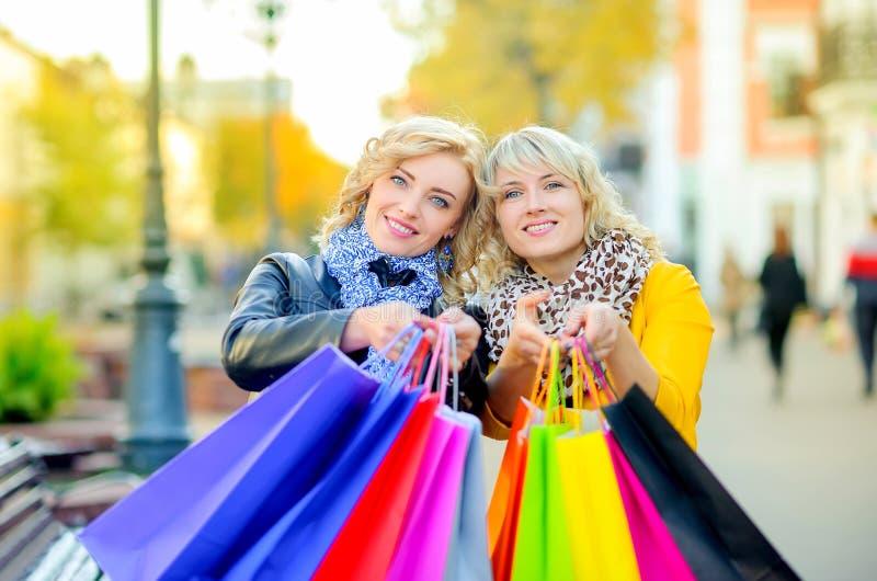Deux filles se tiennent avec des sacs à provisions et sourient, des émotions positives images libres de droits