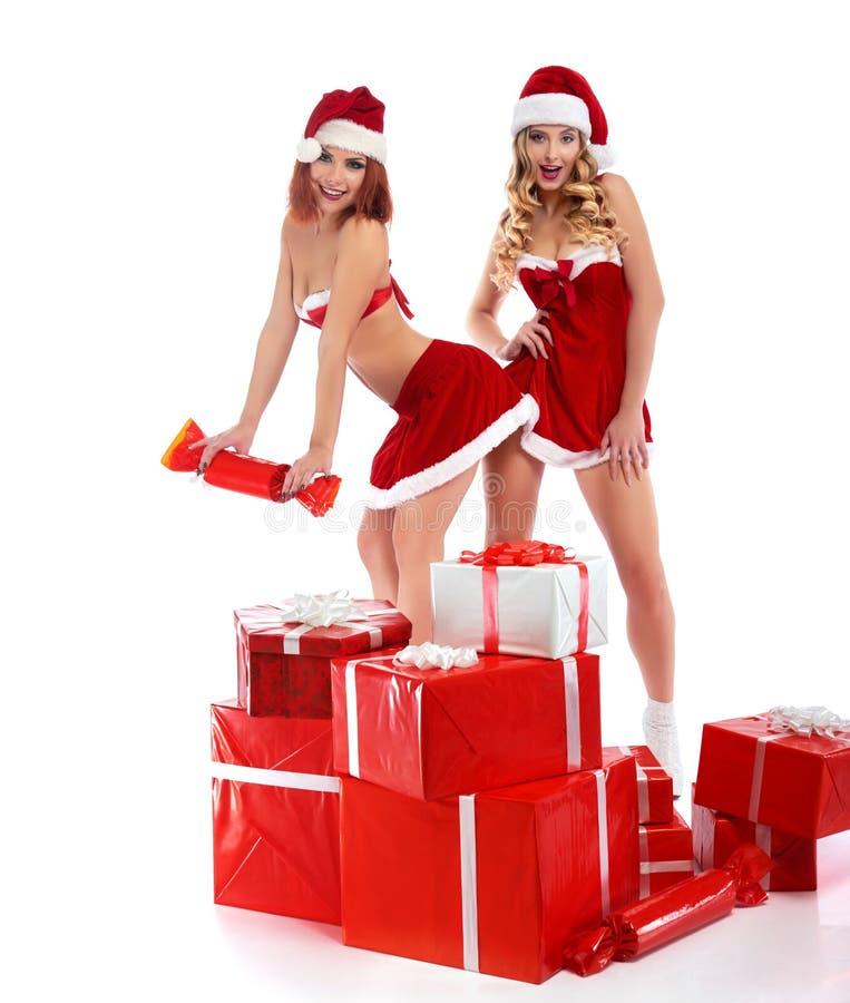 Deux filles sexy de Noël posant avec une pile des présents photo stock
