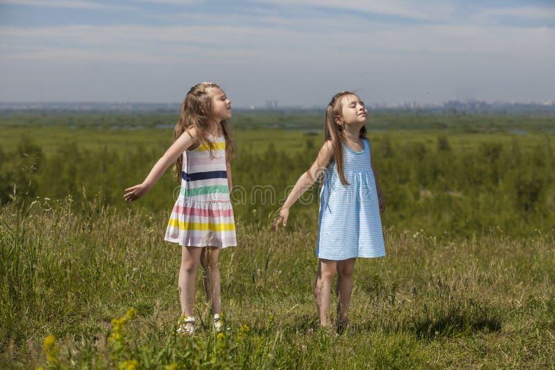 Deux filles sont de jolis enfants en nature souriant heureusement dans le s image libre de droits