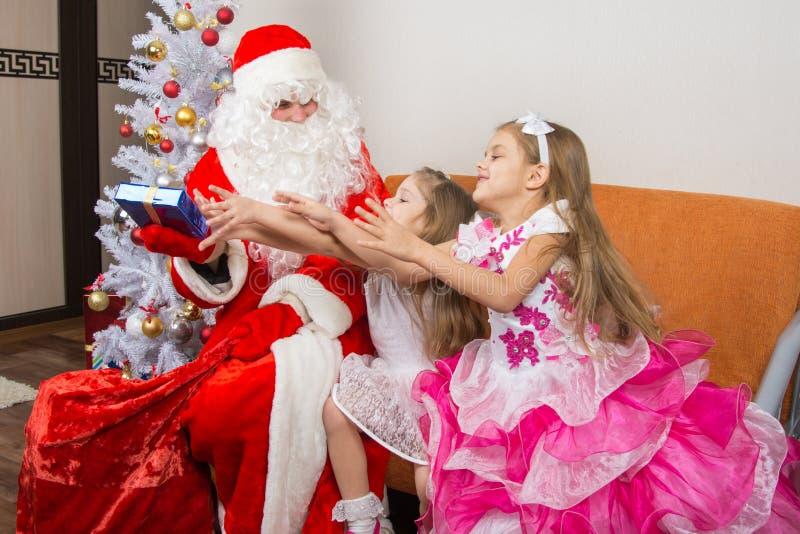 Deux filles sont dessinées pour le cadeau qui a pris le grand-père Frost photos libres de droits