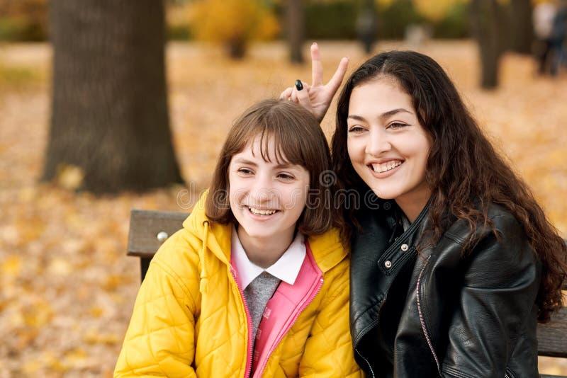 Deux filles sont en parc de ville d'automne image stock