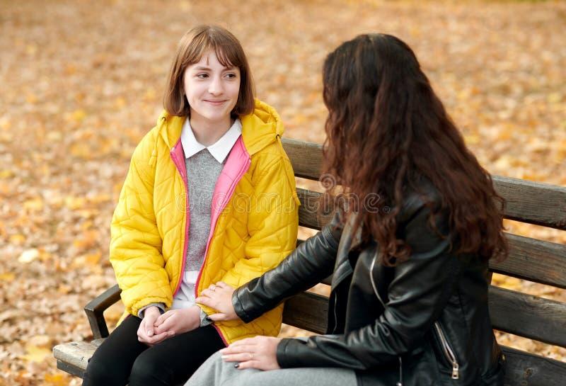 Deux filles sont en parc de ville d'automne Ils parlent photos stock