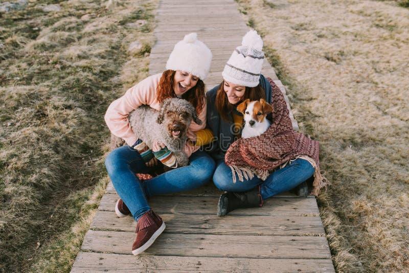 Deux filles sont enveloppées dans une couverture tout en jouant avec leurs chiens dans le pré images stock