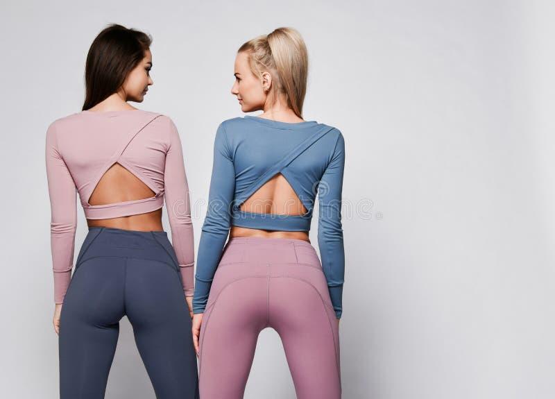 Deux filles sportives de blonde et de brune dans le support sportif de tissu d'usage de sport de tissu de corps ensemble apr?s s? photo libre de droits