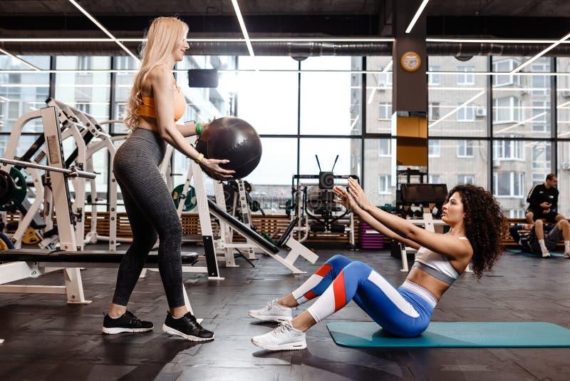 Deux filles sportives habill?es dans des v?tements de sport font des exercices pour la presse sur le tapis pour la forme physique photo libre de droits
