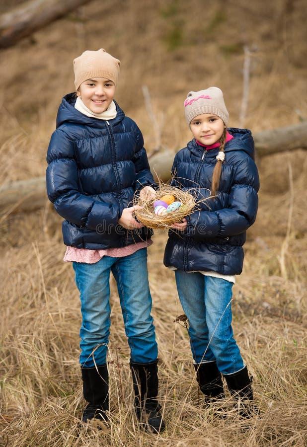 Deux filles sur la chasse à oeuf de pâques à la forêt images stock