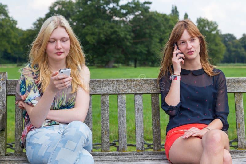 Deux filles sur le banc en parc appelle le mobile image libre de droits