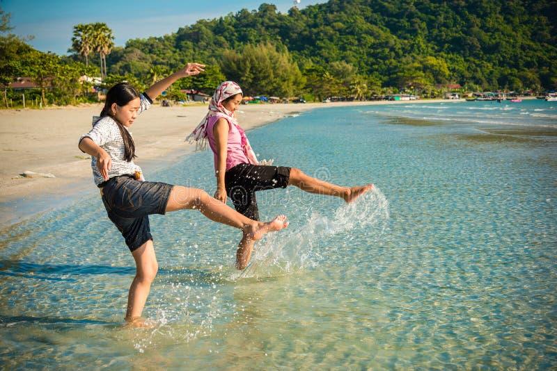 Deux filles thaïlandaises asiatiques donnent un coup de pied la mer le long de la plage image stock