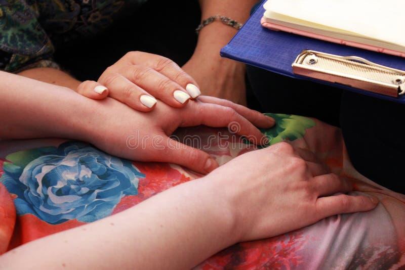 Deux filles tiennent les mains de chacun pendant un cours de formation Deux filles tiennent des mains sur un cours sur enseigner  photos stock