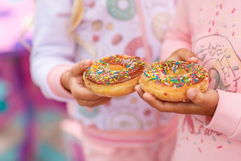 Deux filles tiennent un beignet doux et grand photographie stock libre de droits
