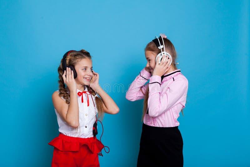 Deux filles utilisant des écouteurs écoutant la musique et la danse image libre de droits