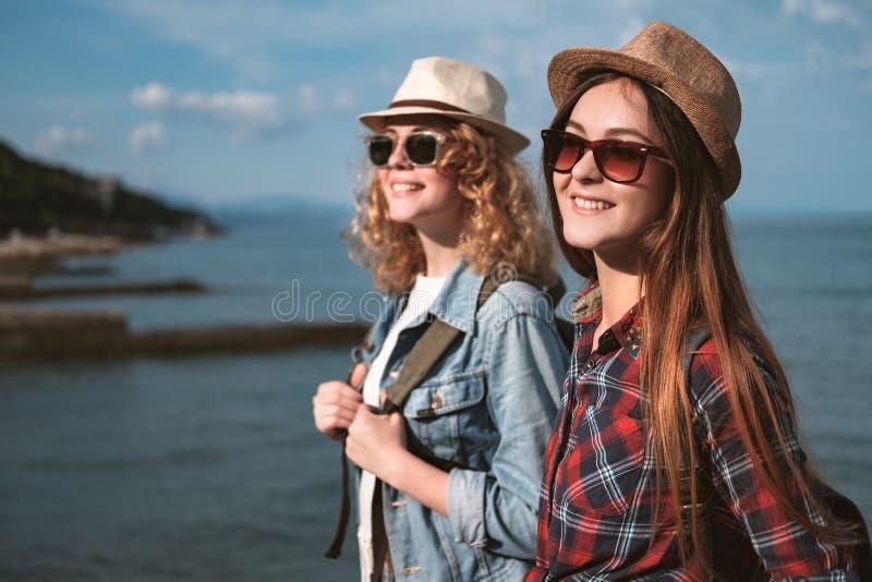 Deux filles voyagent le long du bord de la mer photos libres de droits
