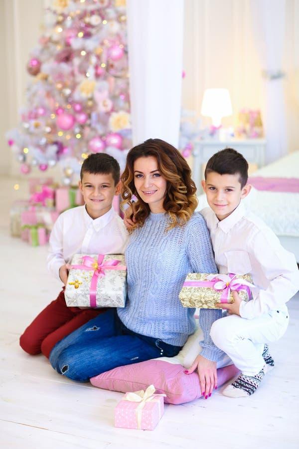 Deux fils s'asseyant avec la mère près de l'arbre de sapin décoré image libre de droits