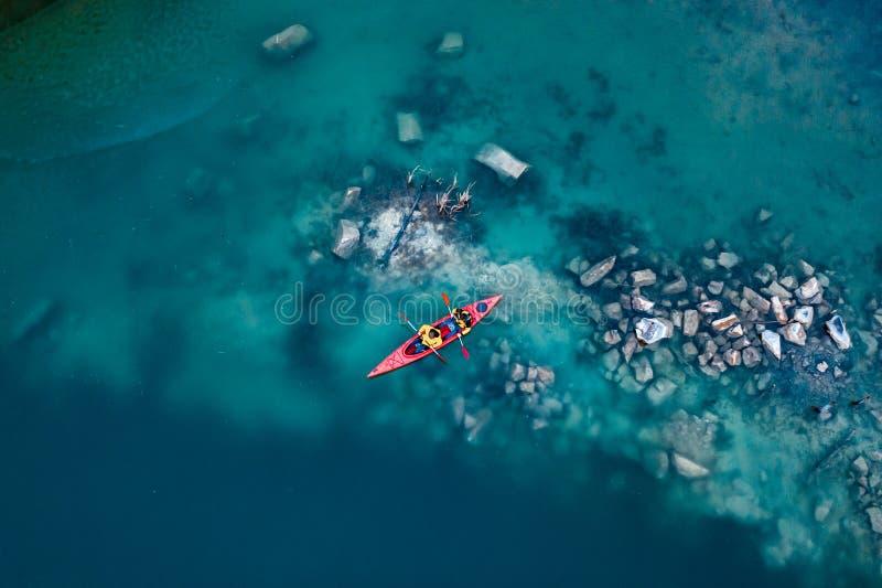 Deux flotteurs sportifs d'homme sur un bateau rouge en rivi?re photo stock