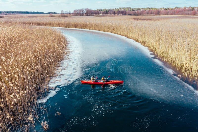 Deux flotteurs sportifs d'homme sur un bateau rouge en rivi?re images libres de droits