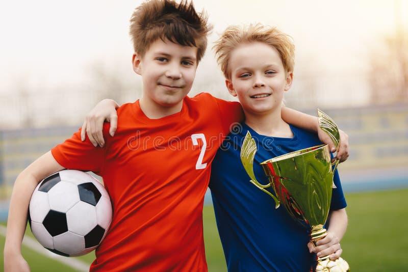 Deux footballeurs heureux de garçons tenant le ballon de football et le trophée d'or images stock