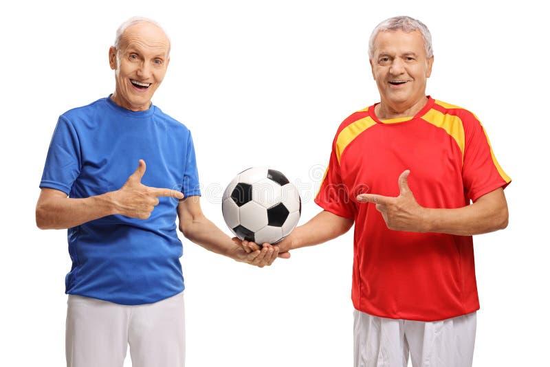 Deux footballeurs pluss âgé tenant un football et un pointage image stock