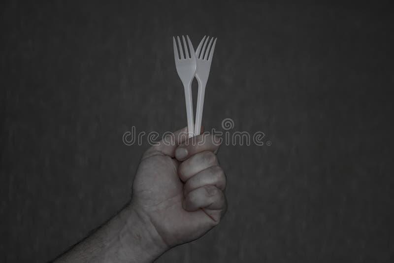 Deux fourchettes jetables blanches dans une main photos libres de droits