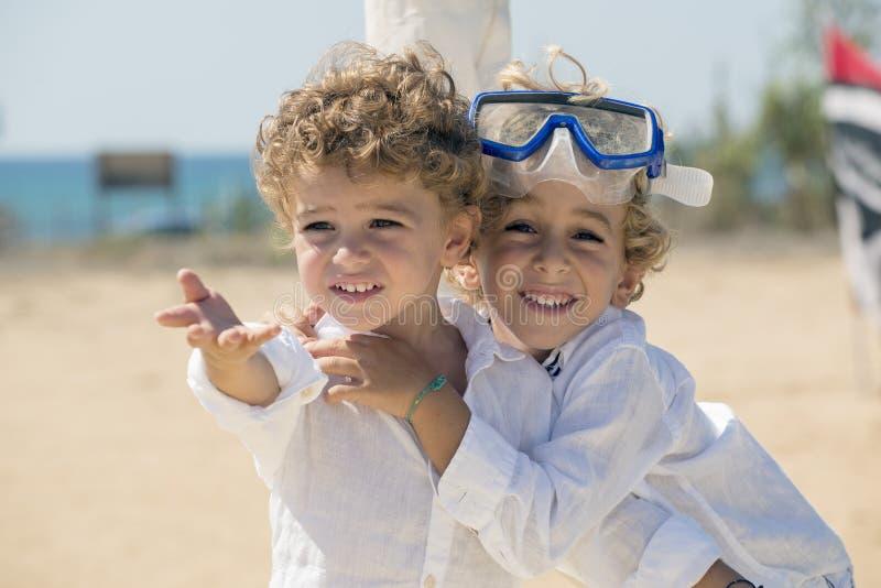 Deux frères blonds jouant sur la plage photographie stock libre de droits