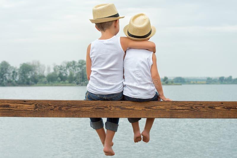 Deux frères dans des chapeaux de paille se reposant sur le pilier et regardant le lac Vacances d'été photographie stock libre de droits