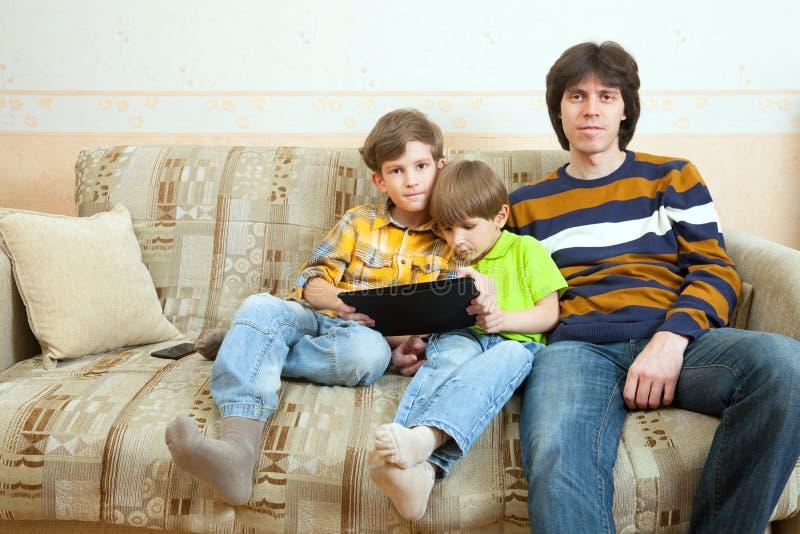 Deux frères et père s'asseyent sur le sofa images stock