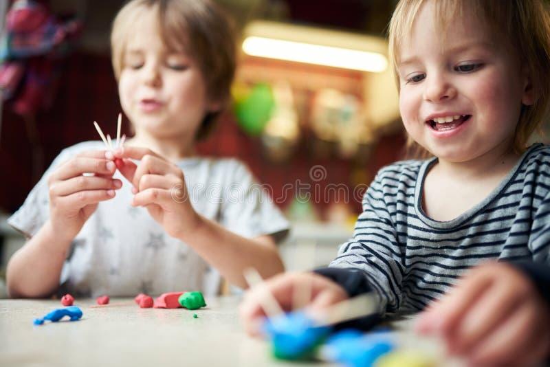 Deux frères font des figures tridimensionnelles de la plasticine et des bâtons photo stock