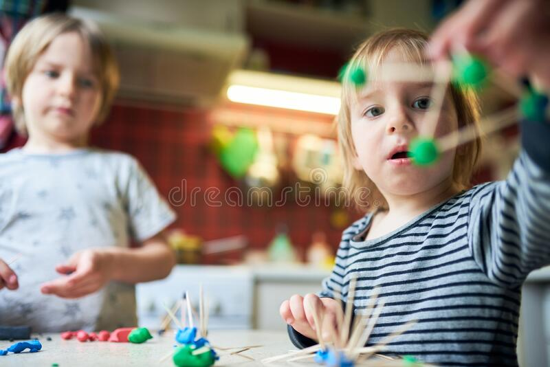 Deux frères font des figures tridimensionnelles de la plasticine et des bâtons photographie stock