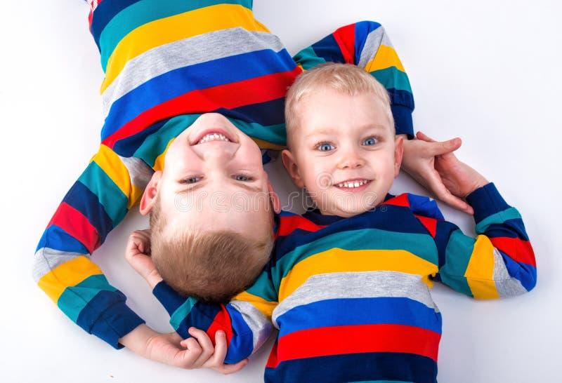 Deux frères jouent, ont l'amusement, font des amis Enfants habillés dans les mêmes vêtements photographie stock