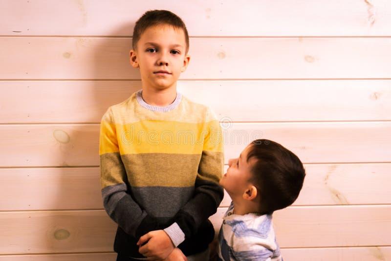 Deux frères - le frère aîné et le jeune frère, parlant dans la maison dans la perspective d'un mur en bois blanc photographie stock libre de droits