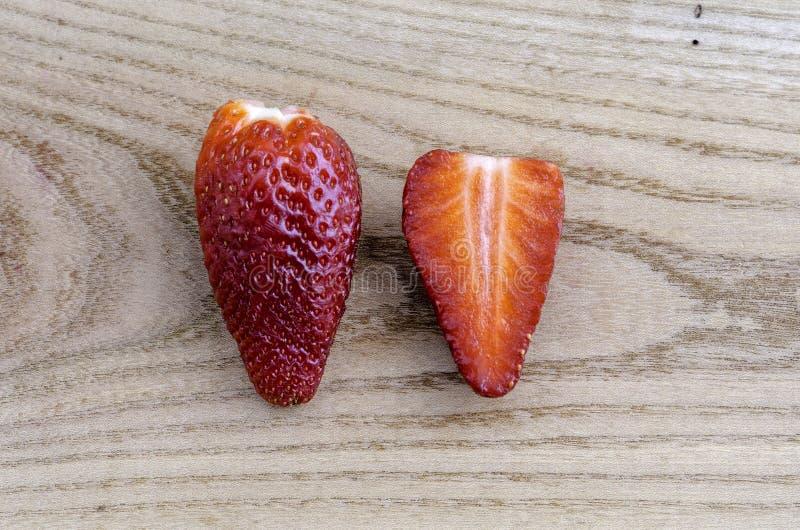 Deux fraises, une fraise coupée dans la moitié photo stock