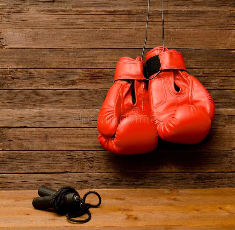 Deux gants de boxe rouges ont accroché sur un fond brun en bois, corde à sauter photo stock