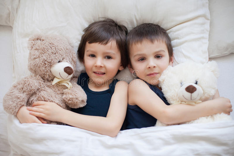 Deux garçons avec des ours de nounours, se situant dans le lit, regardant l'appareil-photo images stock