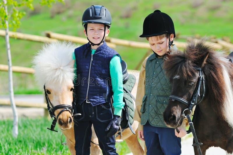 Deux garçons avec des poneys photographie stock