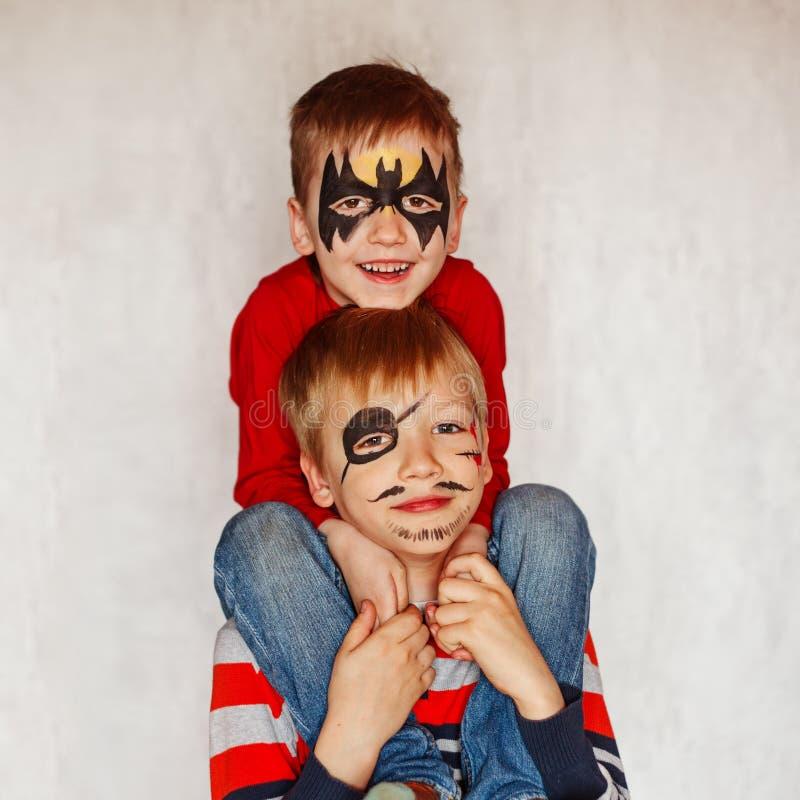 Deux garçons avec l'art de visage d'un héros et d'un pirate Avoir leurs visages photos stock