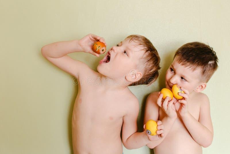 Deux garçons avec le torse nu tenant Pâques ont peint des oeufs photographie stock