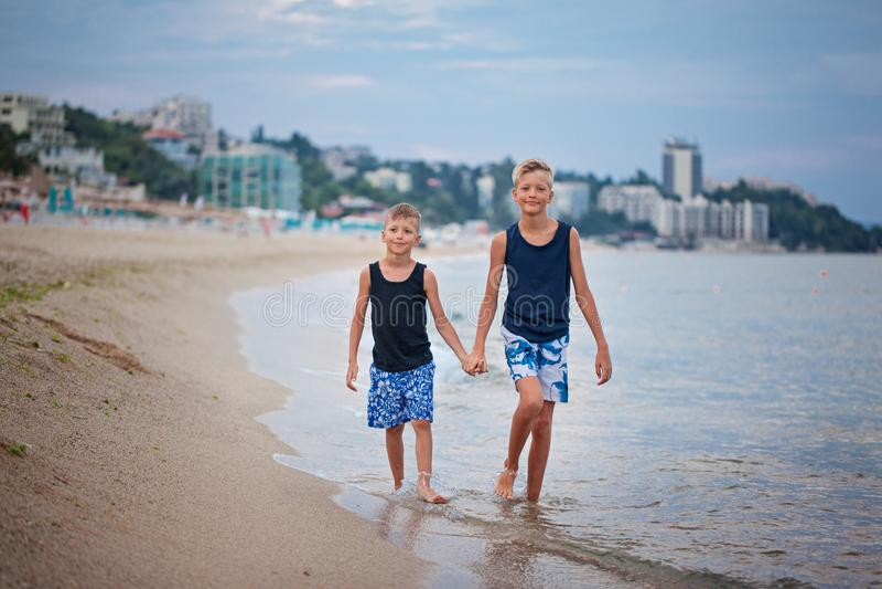 Deux garçons d'enfants marchant sur la mer échouent l'été, jouer heureux de meilleurs amis image libre de droits