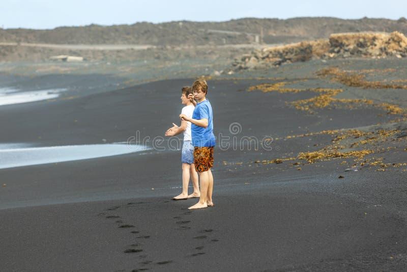 Deux garçons de l'adolescence ont l'amusement à une plage volcanique noire photos libres de droits
