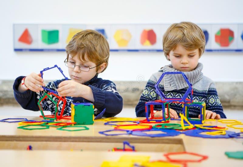 Deux garçons de petit enfant établissant les chiffres géométriques image libre de droits